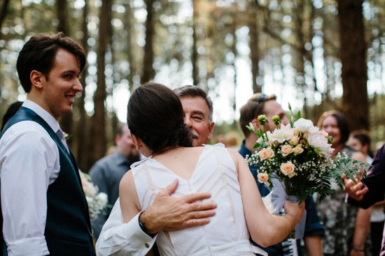 Bride being hugged at forest wedding