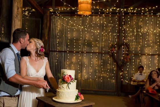 Cutting wedding cake at rustic wedding venye