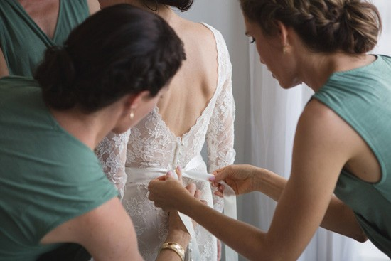Tying bow on brides gown