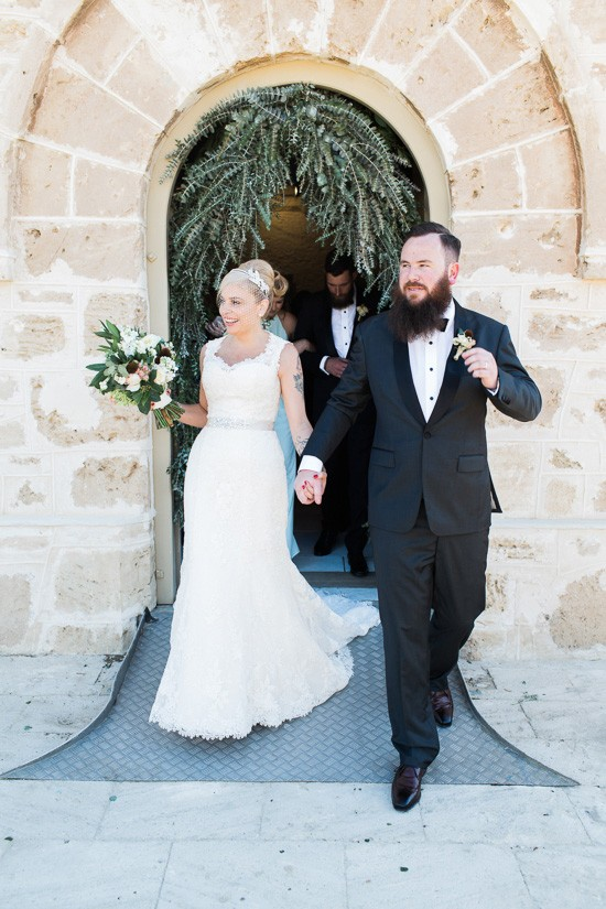 newlyweds in frotn of sandstone building
