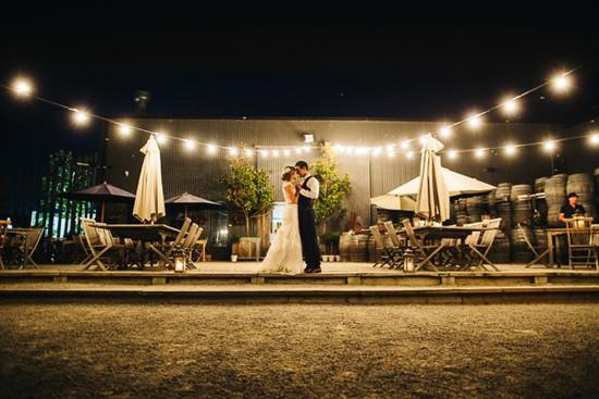Bride and groom at night under festoon lighting