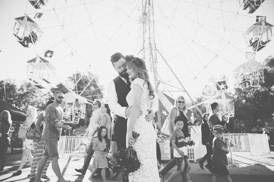 Bride and groom in front of ferris wheel