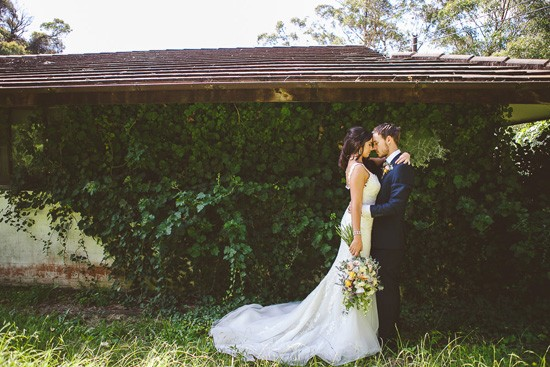 Bride and groom in front of ivy covered wall