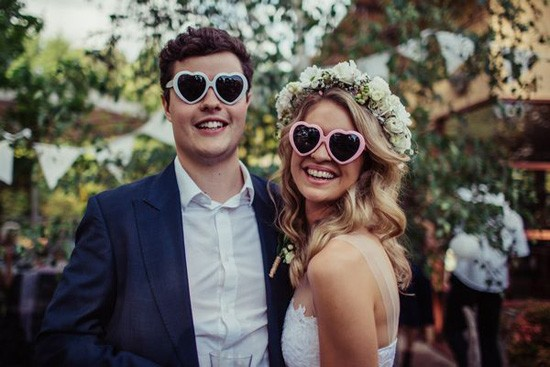 Bride and groom in heart sunglasses