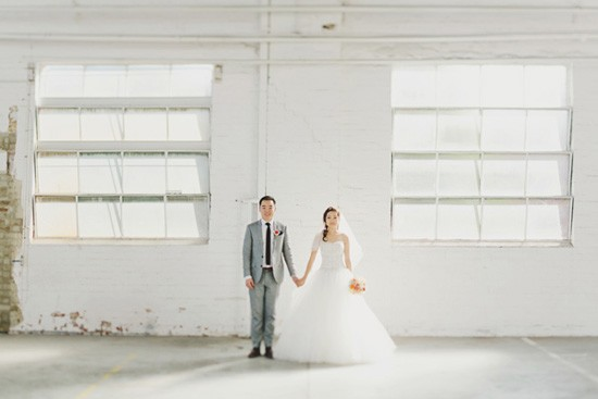 Bride and groom in white industrial space