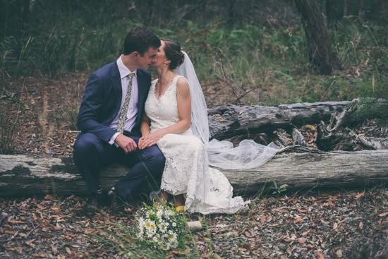 Bride and groom on log