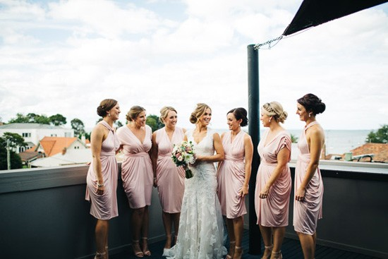 Bride with bridesmaids in pink draped dresses