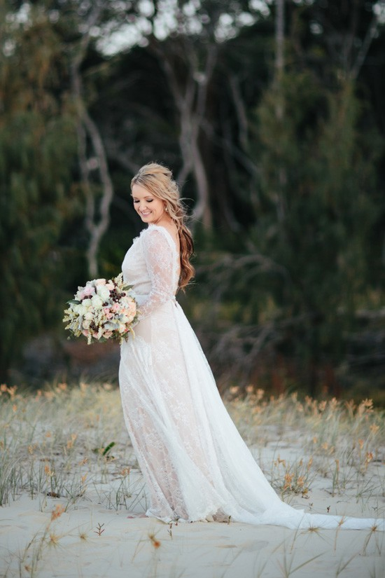 Bride with long sleeve gown at beach