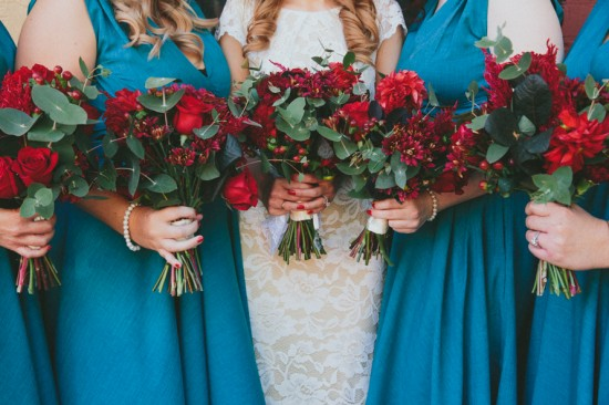 Bridesmaids in teal with red bouquets