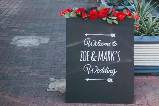 Chalkboard wedding sign with red flowers