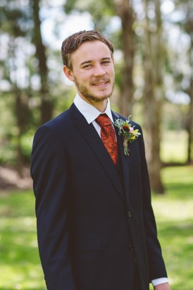 Groom in burnt orange tie