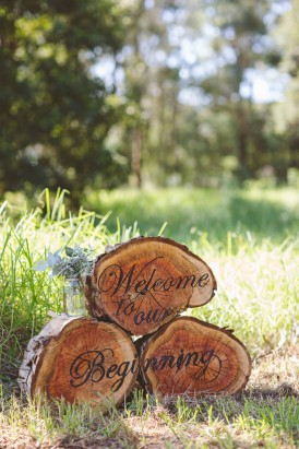 Welcome sign on logs for wedding