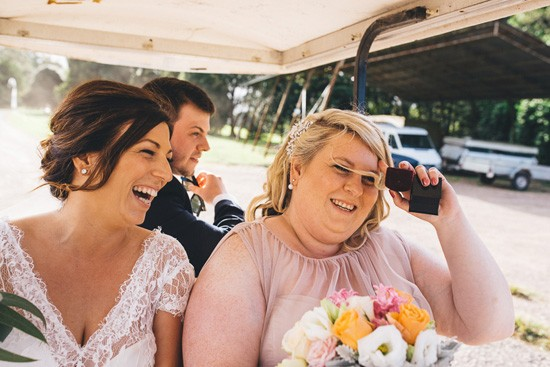Bride and bridesmaid on gold cart