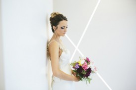 Bride in front of white wall with bouquet
