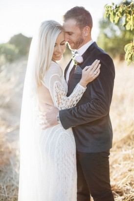 Bride in long sleeve gown with groom in velvet