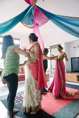 Bride putting on sari
