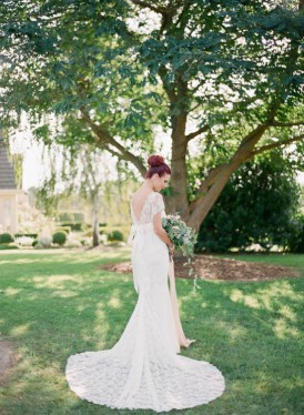 Bride with lace train under tree