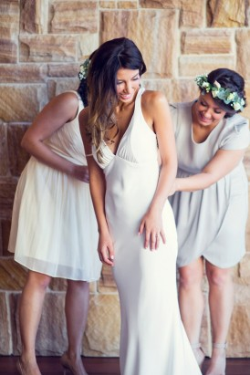 Bridesmaids helping bride with wedding gown