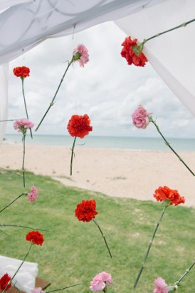 Ceremony backdrop of red and pink hanging flowers