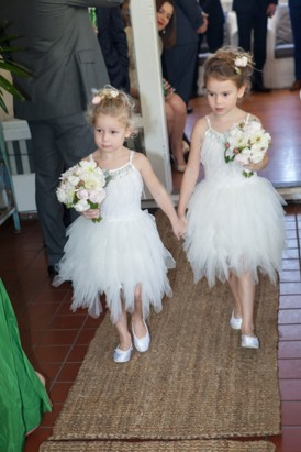 Flowergirls holding hands as they walk down the aisle