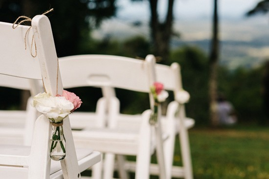Flowers hanging on ceremony chairs