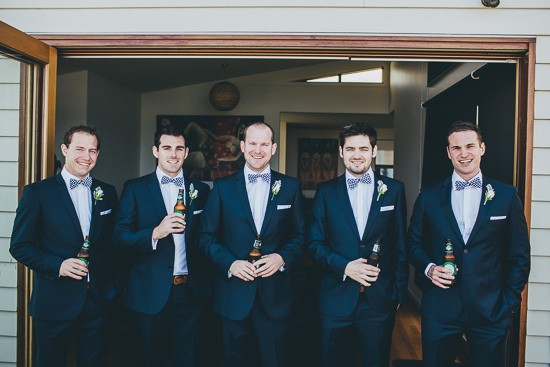 Groom and groomsmen in navy suits with bow ties