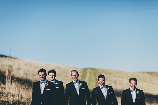 Groom and groomsmen with blue suits and bow ties