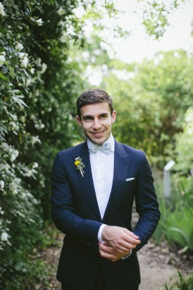Groom in navy suit with bow tie