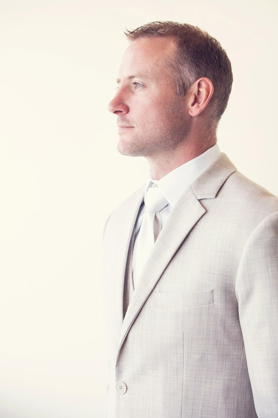 Groom in taupe suit with white tie
