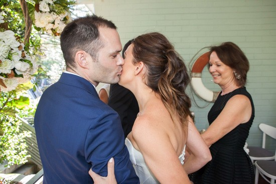 Groom kissing bride on cheek at ceremony