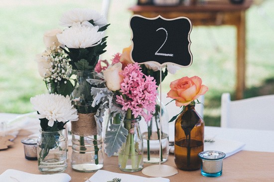 Mismached bottles with flowers at wedding