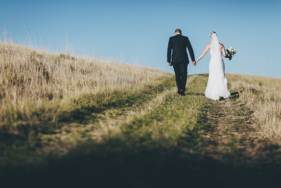 Newlyweds walking up hill