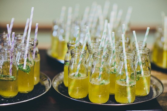 Yellow wedding drinks in glass bottles