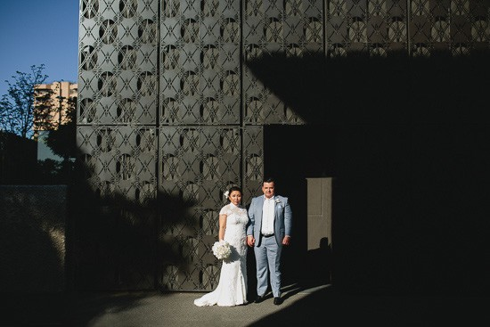 Bride and groom against textured wall
