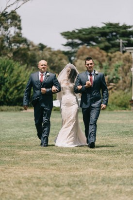 Bride walking down the aisle with brothers