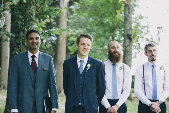Groom and groomsmen watching bride walk down the aisle