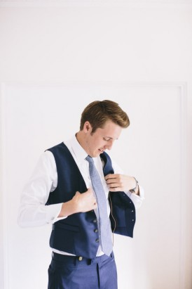 Groom putting on waistcoast