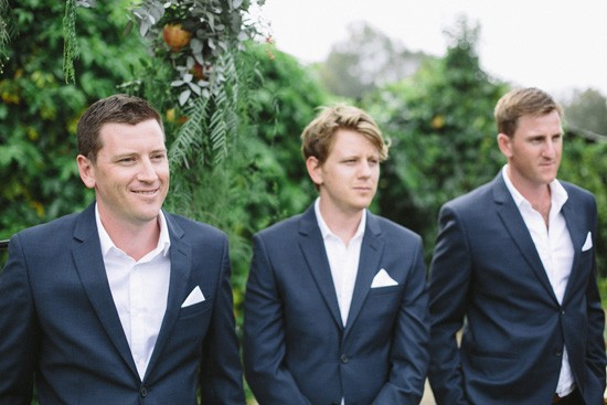 Groomm in navy suit with white shirt