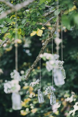 Hanging bottles with flowers at wedding ceremony