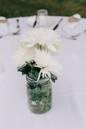 White flowers in glass jar wedding centrepiece
