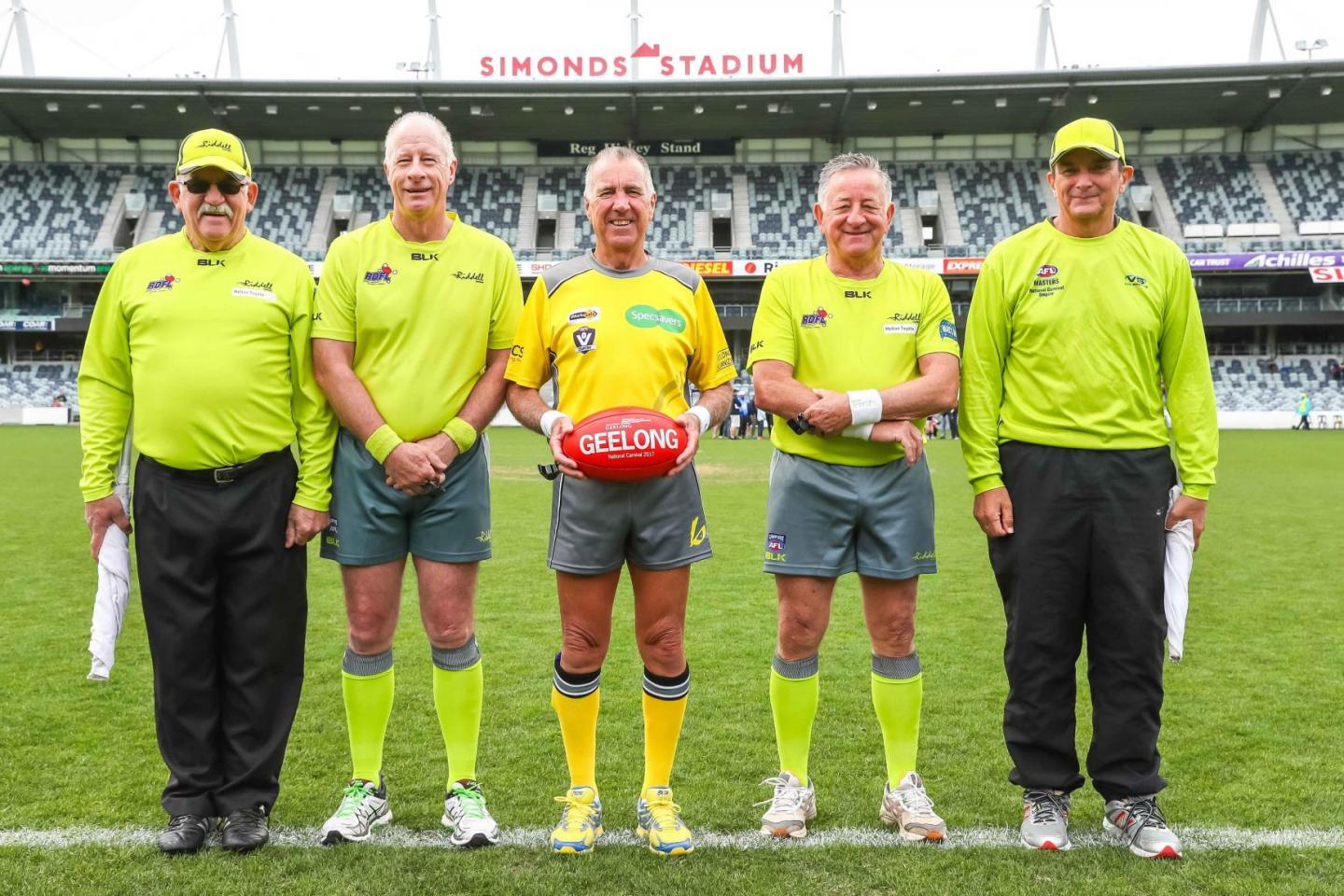 Some AFL Masters standing with a football