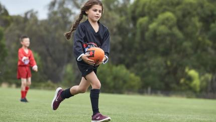 A girl running with a footy ball