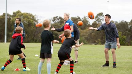 Coaches passing footy balls to kids in a fun activity!