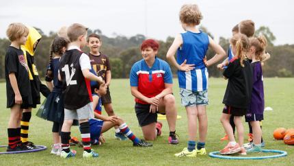 An Auskick Coordinator speaking with some kids.