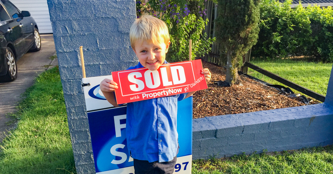 child holding sold sign