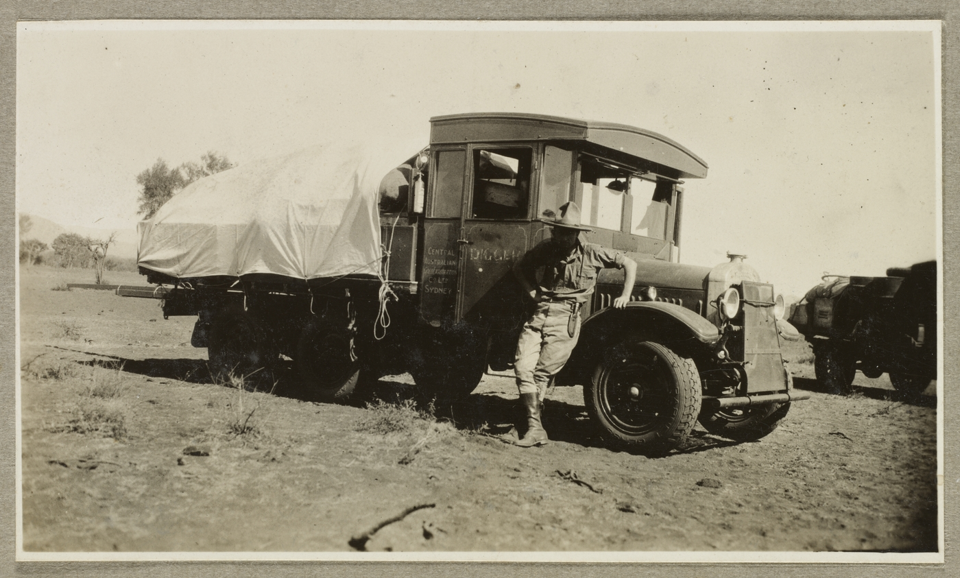 Old photograph of man wearing outdoor clothing with a had leaning against a truck which has a contents on the back with a cover over it