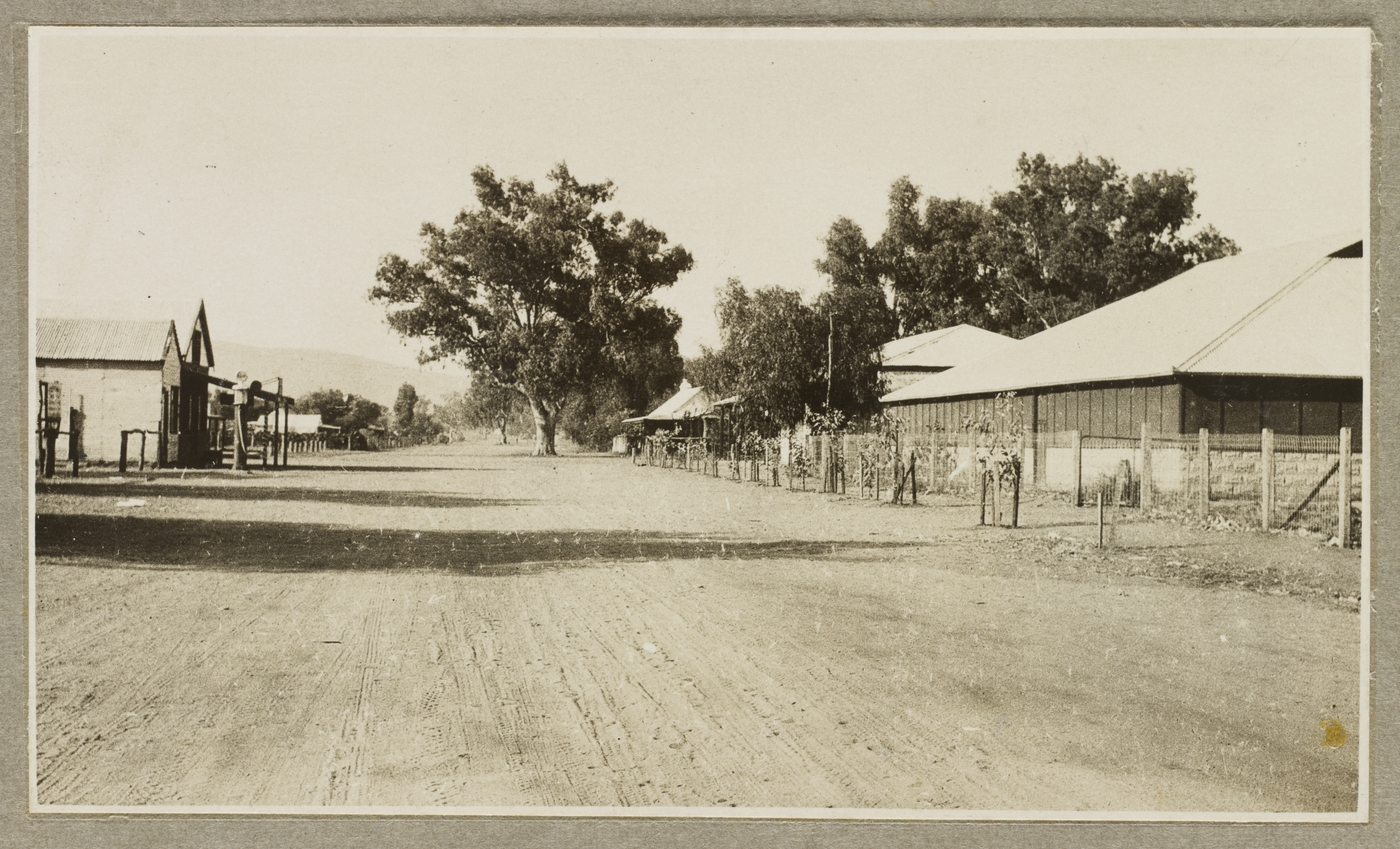 Old photograph of a dirt street in a town with trees and homes