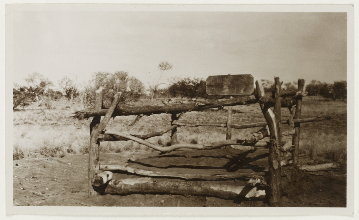 old photograph of logs built into a square that represents a gravesite