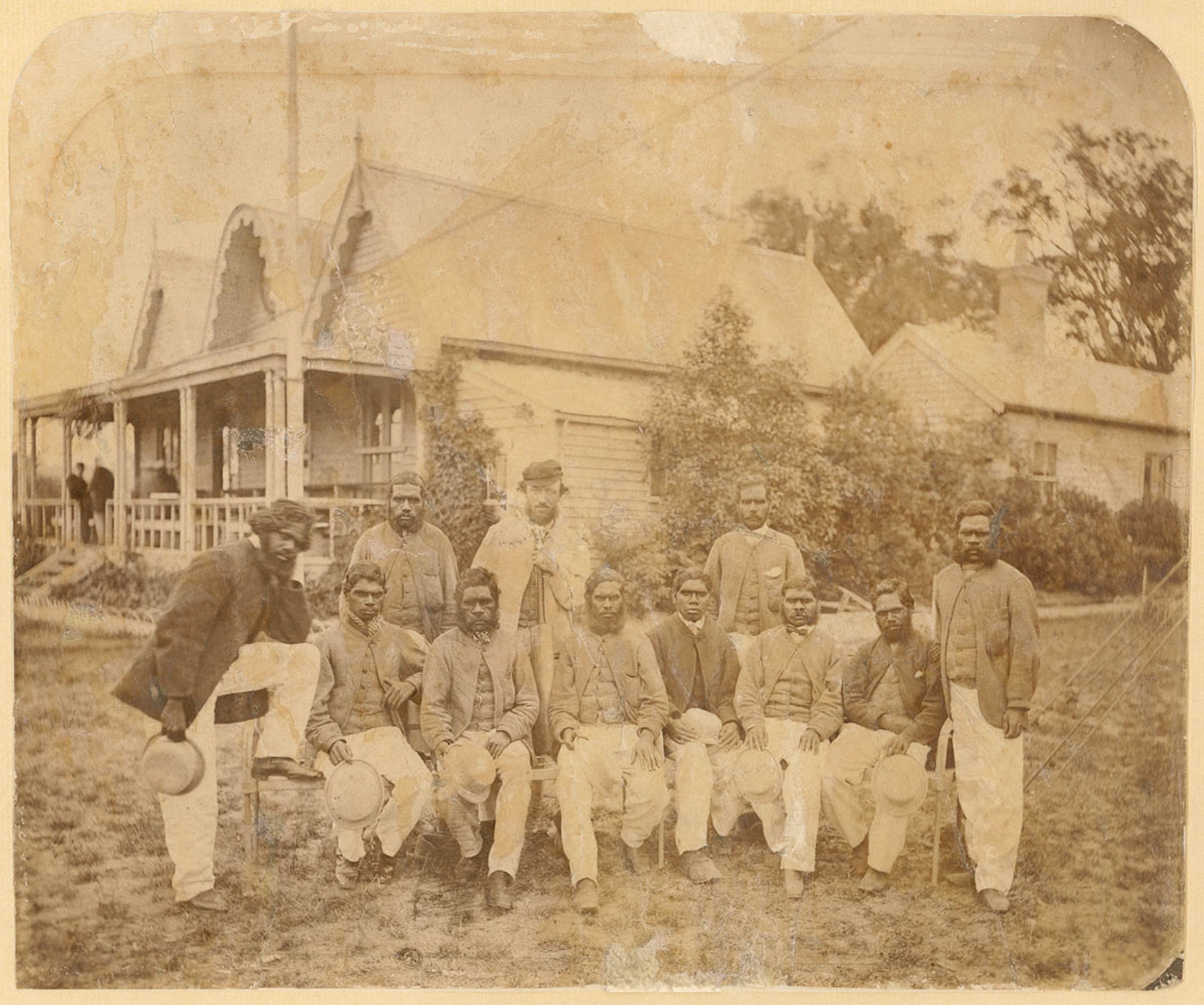 Indigenous Australian cricket team seated outside an old building with their hats