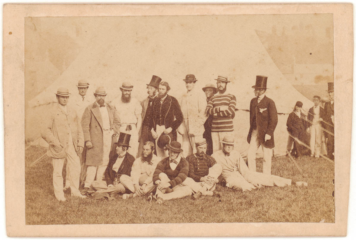 Old portrait of a cricket team wearing hats standing and seated on grass